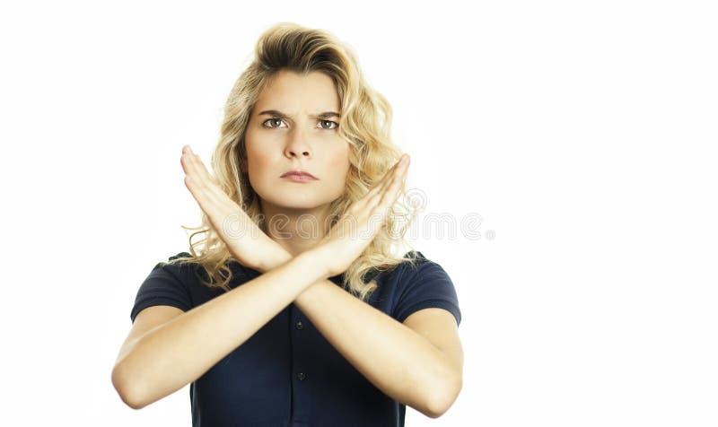 Retrato de uma mulher séria que guarda um par de mãos cruzadas, não mostrando nenhum sinal, isolado em um fundo branco imagem de stock royalty free