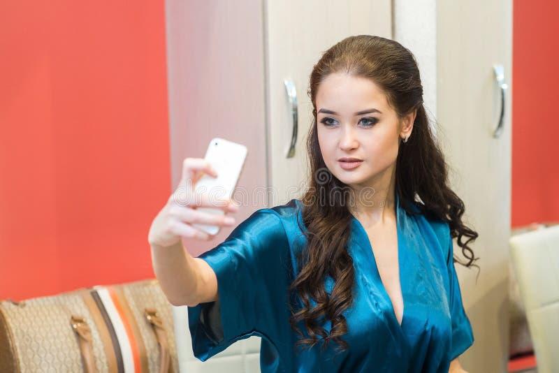 Retrato de uma mulher sensual bonita no roupa interior com o telefone em sua mão fotografia de stock