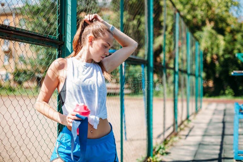 Retrato de uma mulher 'sexy' nova desportiva com uma garrafa da água fresca no campo de esportes do verão Conceito saudável do es fotos de stock