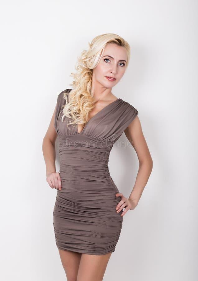 Retrato de uma mulher 'sexy' nova impressionante que levanta em pouco vestido cinzento imagens de stock