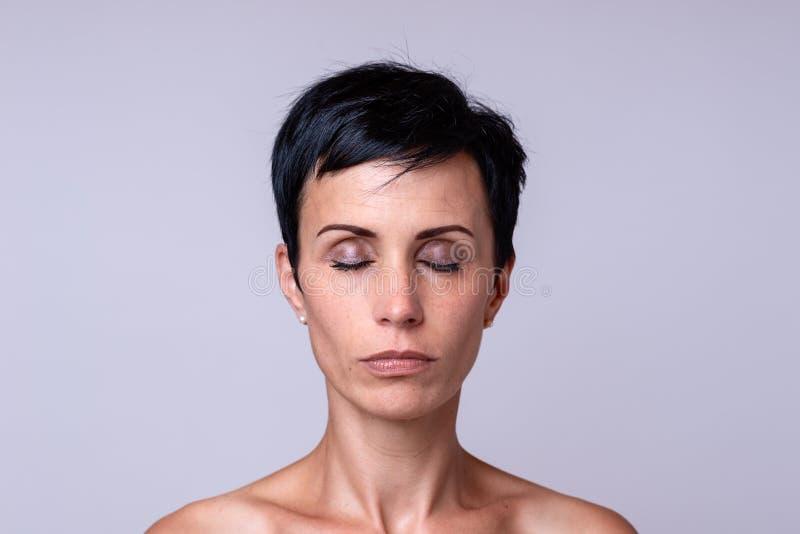 Retrato de uma mulher sobre o fundo neutro fotos de stock royalty free