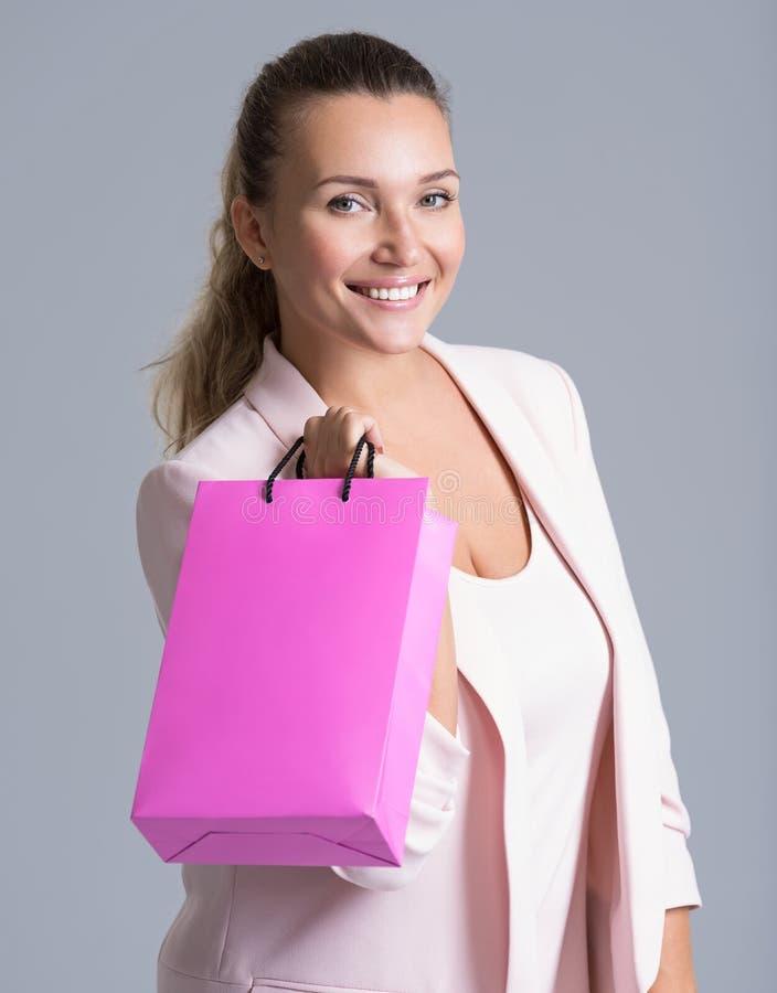 Retrato de uma mulher de sorriso feliz com saco de compras cor-de-rosa imagem de stock royalty free
