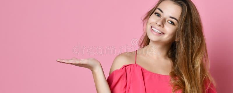 Retrato de uma mulher de sorriso feliz que guarda o copyspace na palma fotografia de stock royalty free