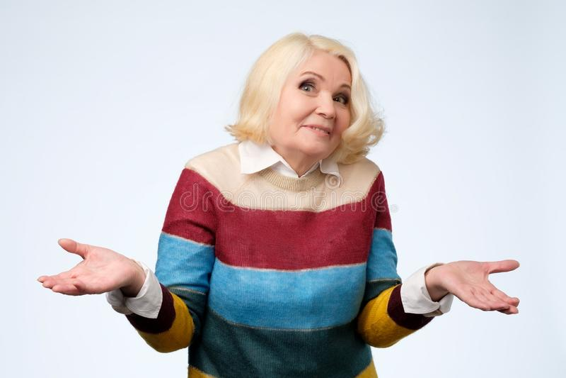 Retrato de uma mulher superior agradável que tem um gesto de dúvida imagens de stock