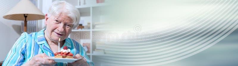 Retrato de uma mulher superior feliz que guarda um bolo de anivers?rio pequeno Bandeira panor?mico fotografia de stock