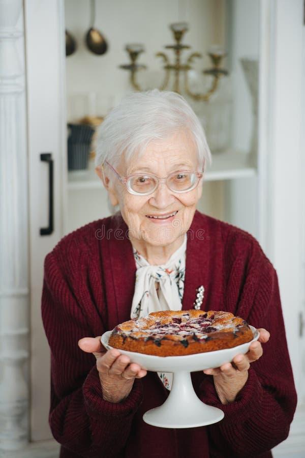 Retrato de uma mulher superior que apresenta a torta saboroso do feriado fotografia de stock royalty free