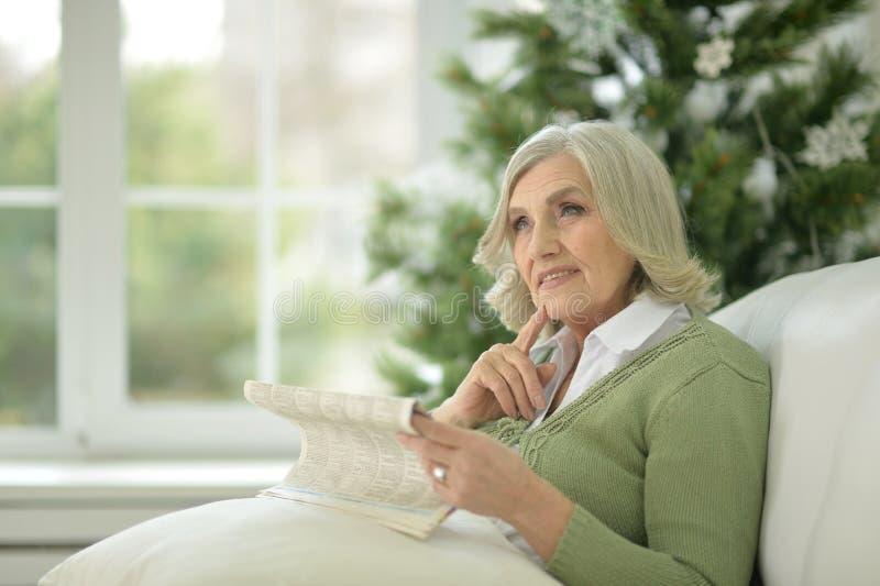 Retrato de uma mulher superior que decora a árvore de Natal fotografia de stock