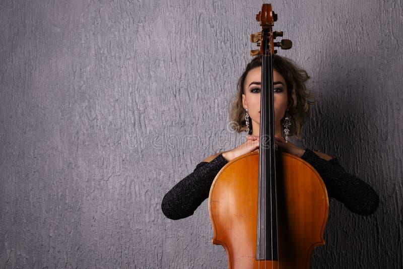Retrato de uma mulher triste nova A parte da cara é coberta pelo pescoço do violoncelo imagens de stock
