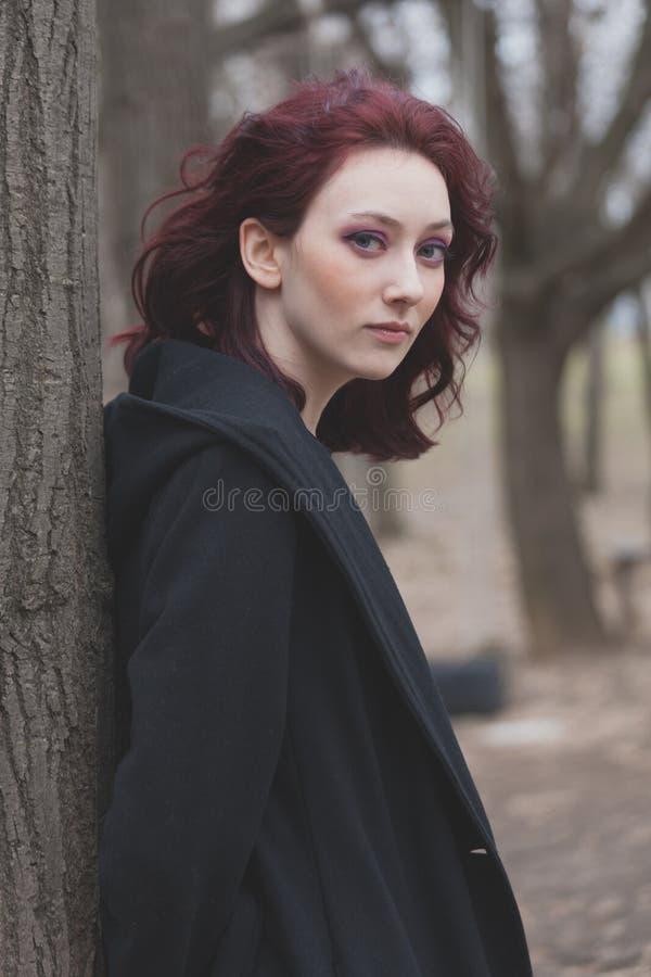 Retrato de uma mulher vermelha pálida nova do cabelo na carne sem gordura preta do revestimento no outono exterior do inverno da  fotos de stock royalty free