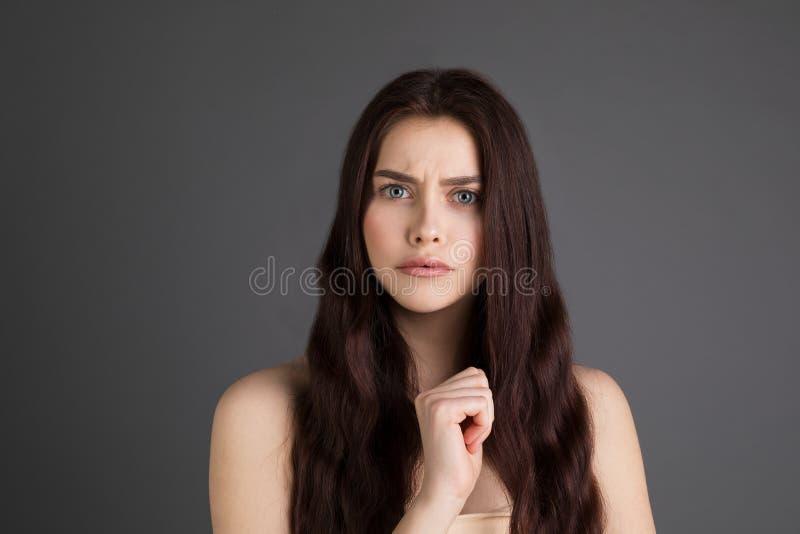 Retrato de uma mulher virada, séria, irritada com cabelo moreno longo imagem de stock