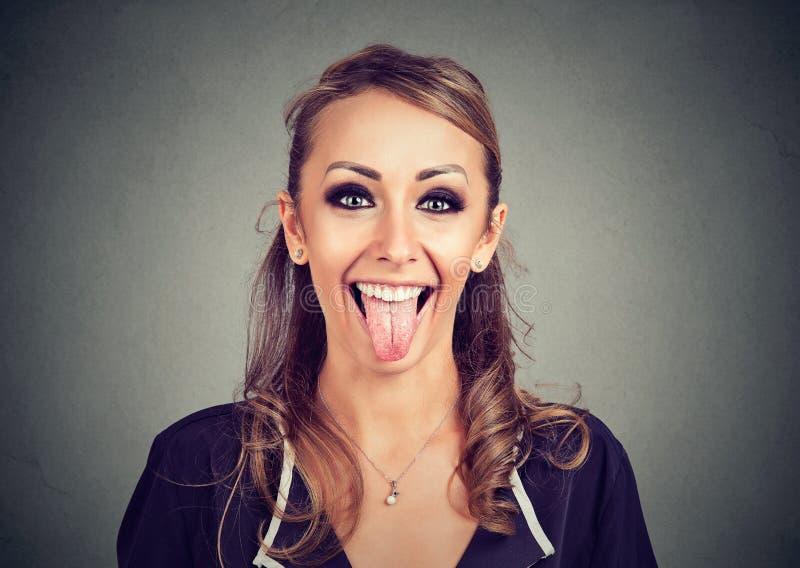 Retrato de uma mulher de vista engraçada nova que mostra sua língua fotografia de stock