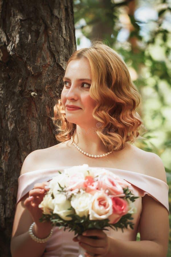 Retrato de uma noiva bonita que está perto de uma árvore imagem de stock
