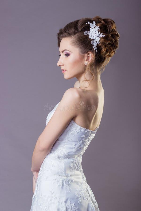 Retrato de uma noiva delicada e elegante bonita das mulheres da menina em um vestido branco com um penteado e uma composição boni fotografia de stock royalty free