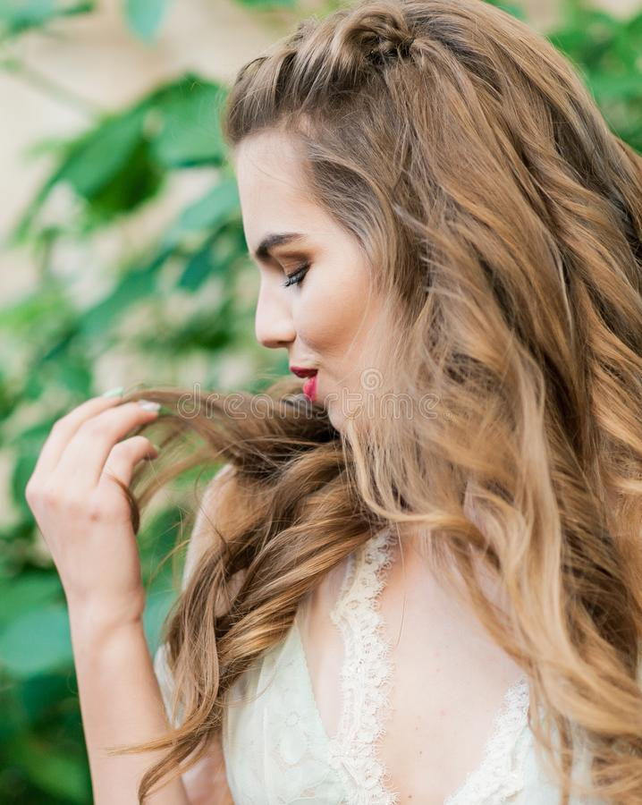 Retrato de uma noiva nova no boudoir branco do laço com cabelo encaracolado ondulado fotos de stock