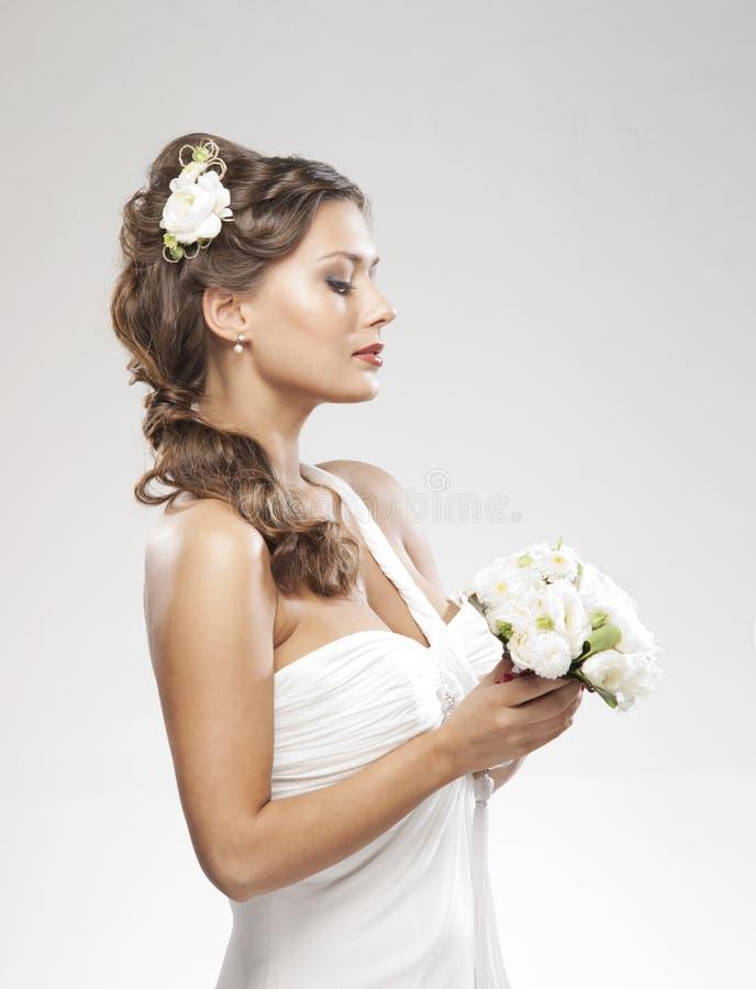 Retrato de uma noiva nova que prende as rosas brancas imagem de stock