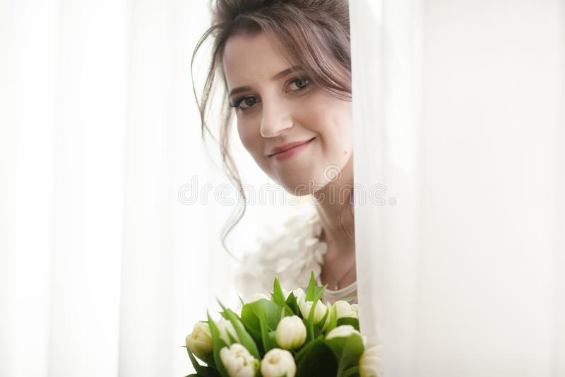 Retrato de uma noiva de sorriso perto da janela fotografia de stock