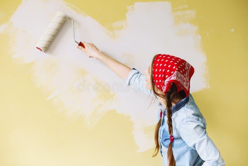 Retrato de uma parede bonita nova da pintura da mulher em seu apa novo imagem de stock royalty free