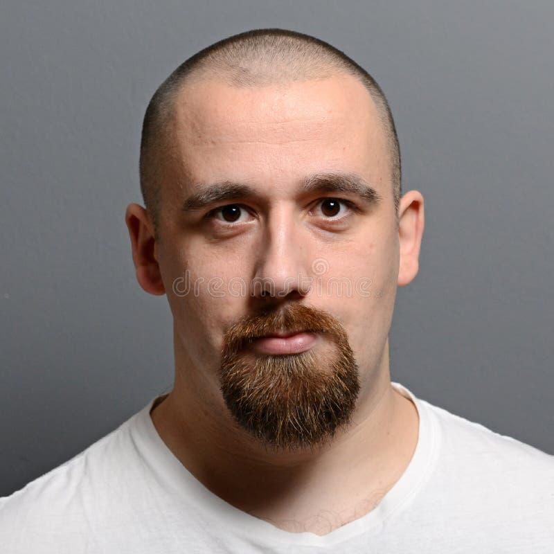 Retrato de uma posição do homem novo contra o fundo cinzento fotos de stock royalty free