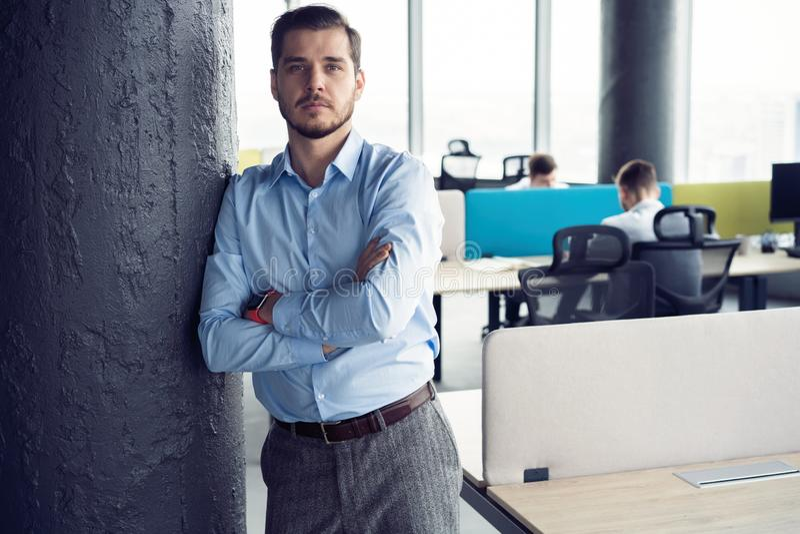 Retrato de uma posição nova ocasionalmente vestida do homem de negócios em um escritório na moda fotos de stock