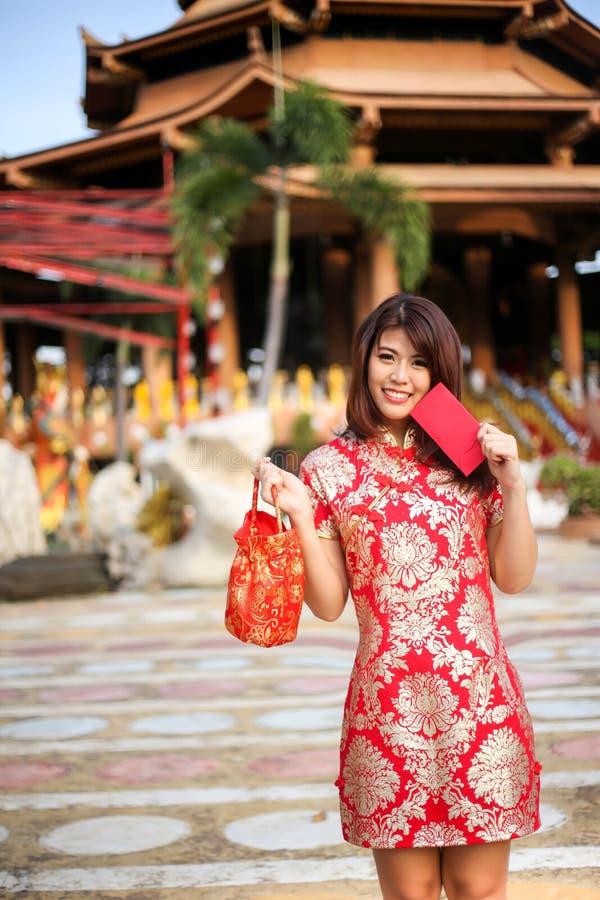 Retrato de uma posse asiática bonita da mulher com dinheiro da sorte e o bolso vermelho, conceito chinês do ano novo fotografia de stock