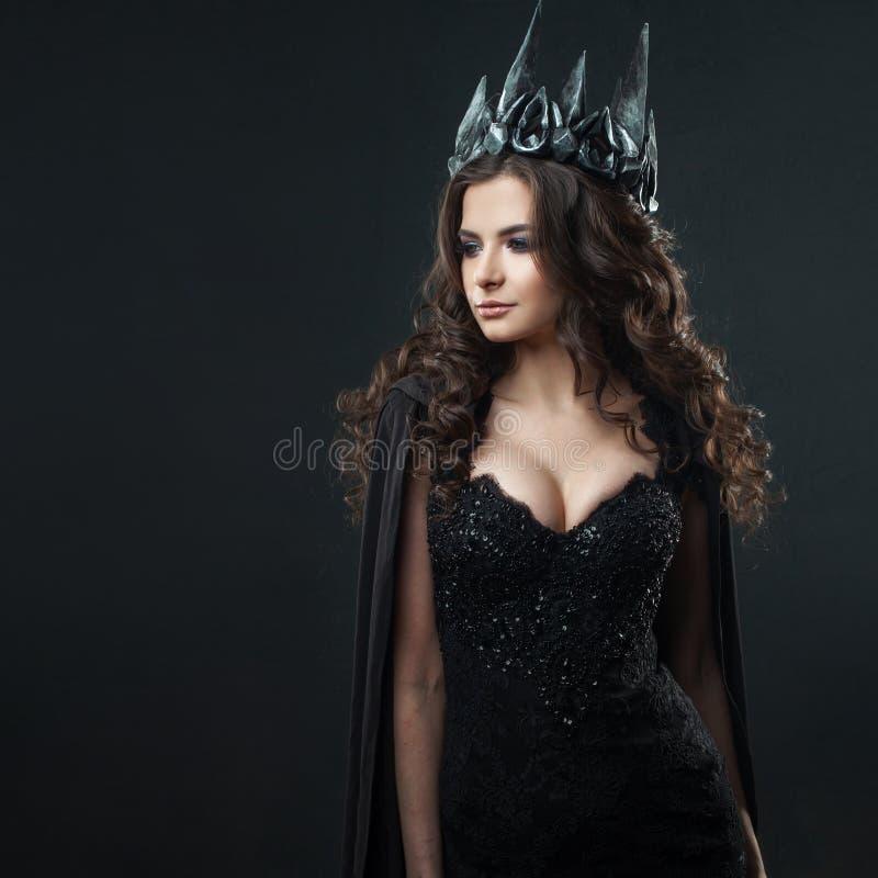 Retrato de uma princesa gótico Mulher moreno nova bonita na coroa do metal e no casaco preto imagem de stock royalty free