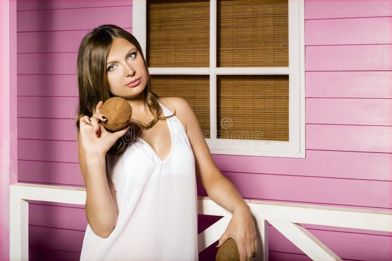 Retrato de uma rapariga bonita a mulher 'sexy' está perto da casa do rosa da praia e guarda cocos em sua mão fotografia de stock royalty free