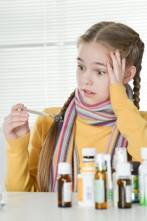 Retrato de uma temperatura de medição da menina doente fotos de stock