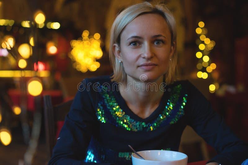 Retrato de un acogedor joven con la taza de café, galleta y luces de la Navidad y rama del pino fotos de archivo libres de regalías
