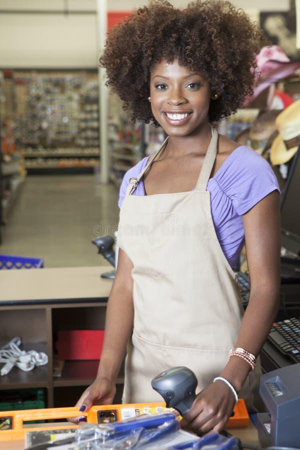 Retrato de un administrativo de sexo femenino afroamericano que se coloca en el contador de pago y envío imagenes de archivo