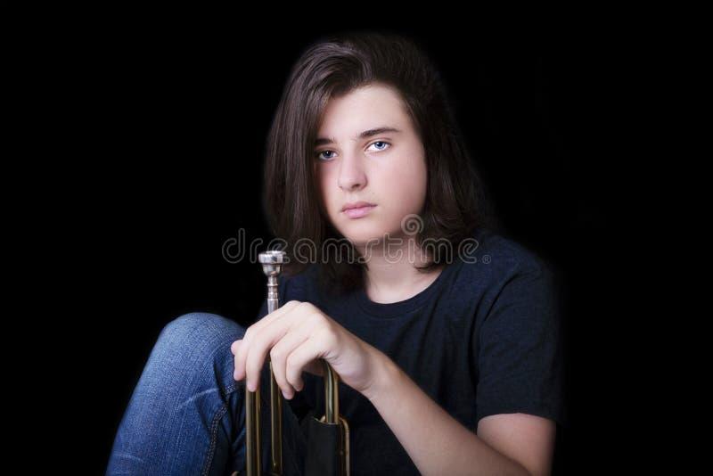 Retrato de un adolescente con la trompeta en estudio foto de archivo