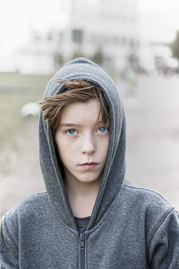 Retrato de un adolescente con los suéteres con capucha grises imagen de archivo