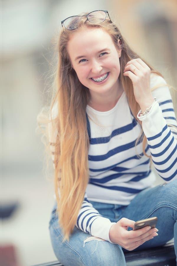 Retrato de un adolescente hermoso sonriente con los apoyos dentales Colegiala joven con el bolso de escuela y el teléfono móvil fotos de archivo