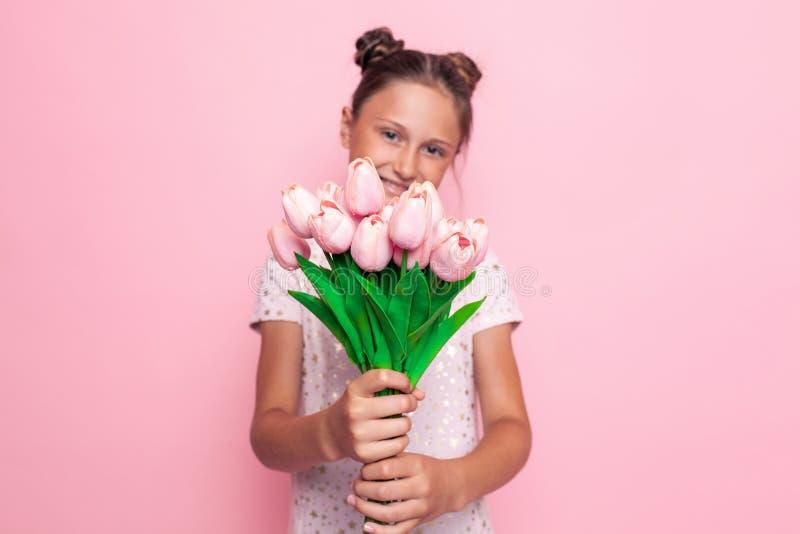 Retrato de un adolescente lindo en un vestido elegante con un ramo de flores fotografía de archivo