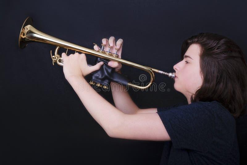 Retrato de un adolescente que toca la trompeta en estudio fotografía de archivo