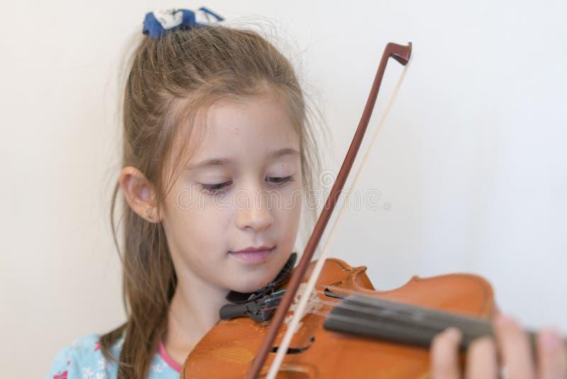 Retrato de un adolescente rubio joven que toca el violín Muchacha que toca el violín en un fondo ligero imagen de archivo libre de regalías