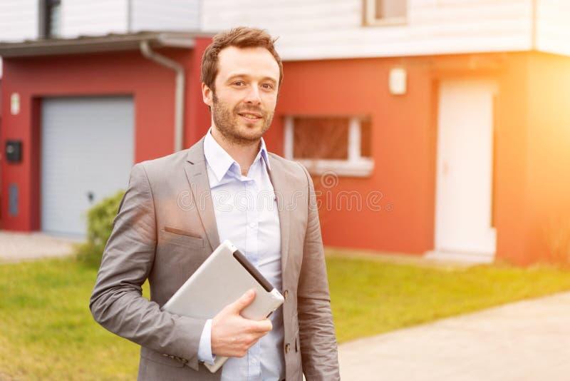 Retrato de un agente inmobiliario joven delante de una casa imágenes de archivo libres de regalías