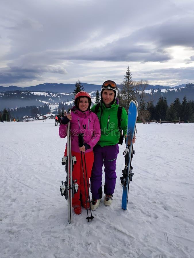Retrato de un amante de un par de esquiadores en un equipo en el top de las monta?as c?rpatas fotos de archivo