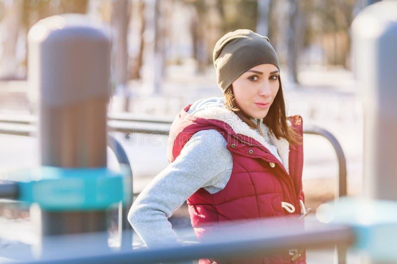 Retrato de un atleta de la muchacha en un sombrero con los guantes y un chaleco caliente al lado de un patio del entrenamiento al imagen de archivo libre de regalías