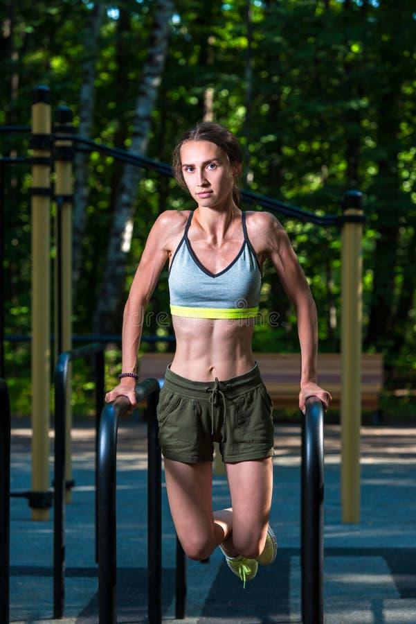 retrato de un atleta que realiza los ejercicios para el aire libre de la prensa en el parque fotos de archivo