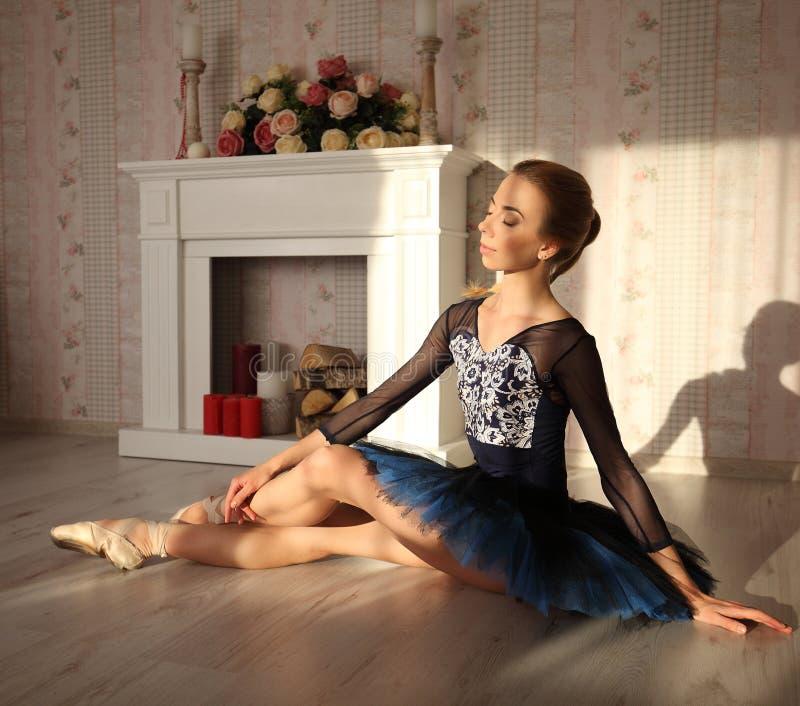 Retrato de un bailarín de ballet profesional que se sienta en el piso de madera en luz del sol Bailarina de sexo femenino que tie fotos de archivo libres de regalías