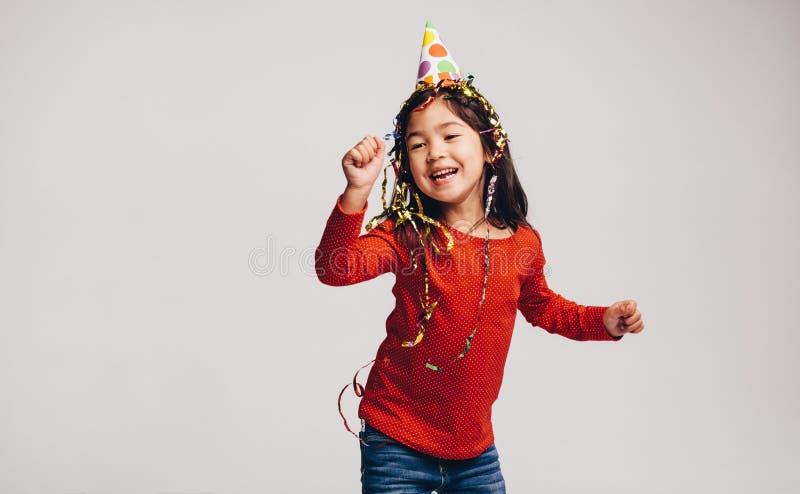 Retrato de un baile feliz del niño que lleva un casquillo y cintas del partido en la cabeza Niño asiático alegre que tiene baile  foto de archivo libre de regalías