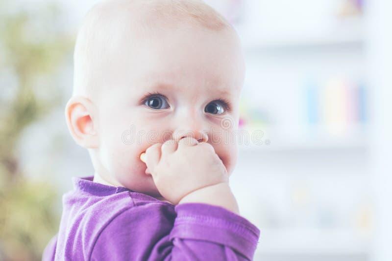 Retrato de un bebé de un año feliz en un fondo del sitio brillante del ` s de los niños fotos de archivo libres de regalías