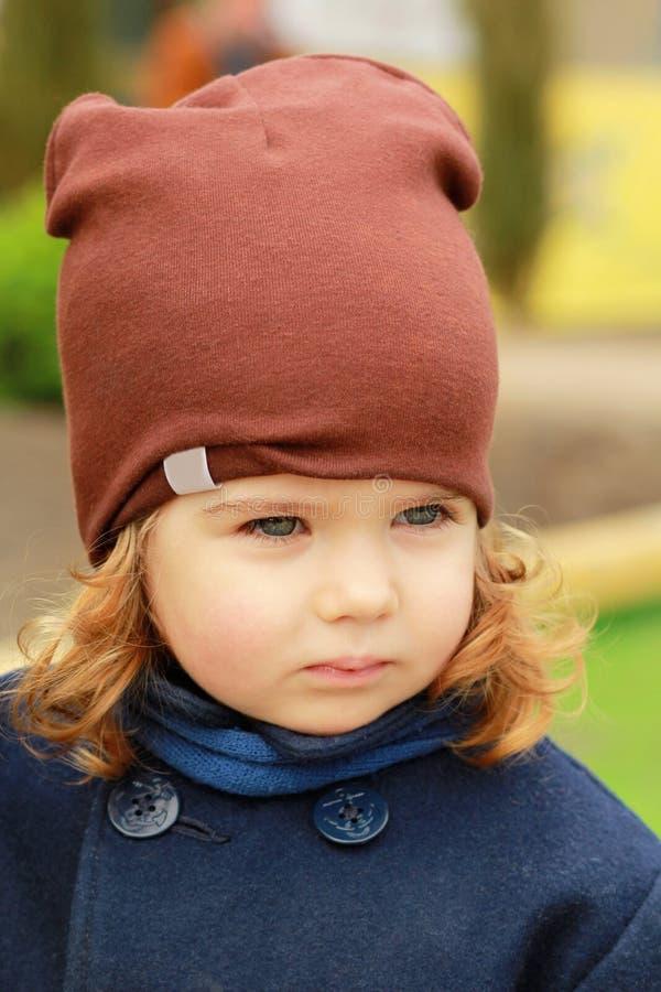 Retrato de un bebé de un año serio elegante lindo que lleva una capa azul marino, la bufanda y un sombrero marrón en un otoño sol fotografía de archivo libre de regalías