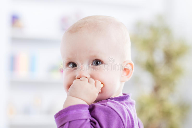 Retrato de un bebé de un año feliz en un fondo del sitio brillante del ` s de los niños fotografía de archivo