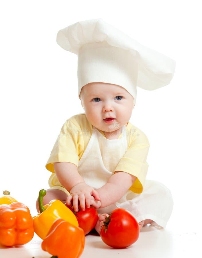 Retrato de un bebé en sombrero del cocinero con el alimento sano fotografía de archivo libre de regalías