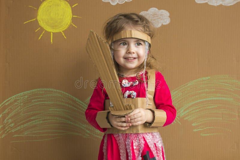 Retrato de un bebé juguetón con una espada de la cartulina y un traje handmade fondo del sol pintado y de las nubes blancas imagen de archivo