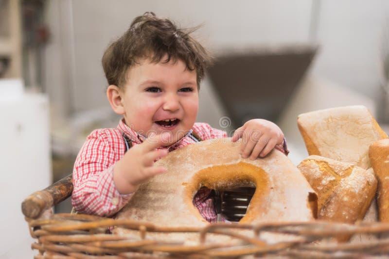 Retrato de un bebé lindo dentro de una cesta con pan en la panadería fotos de archivo