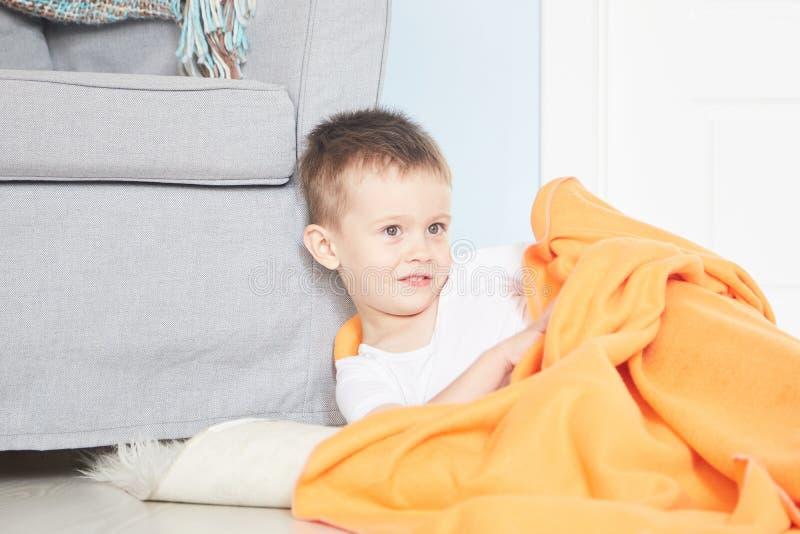 Retrato de un bebé lindo en tela escocesa anaranjada en hogar imagen de archivo libre de regalías