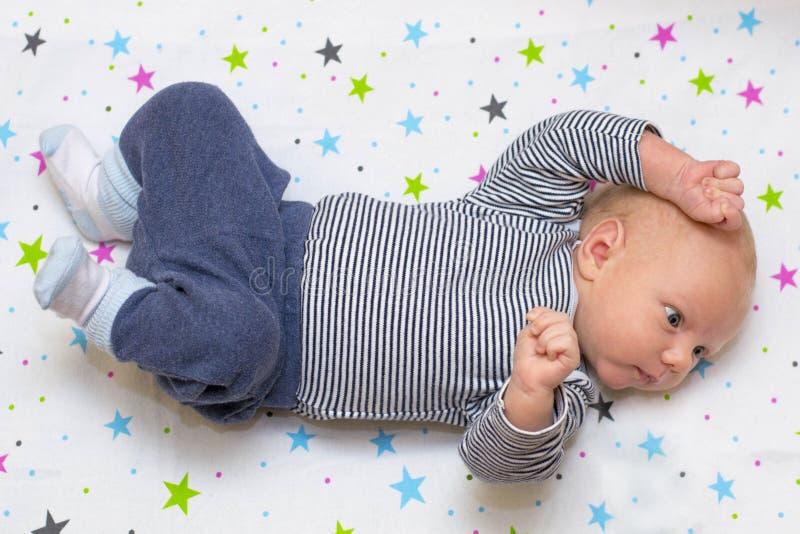 Retrato de un bebé recién nacido lindo que miente en el suyo detrás en pesebre, a imagen de archivo
