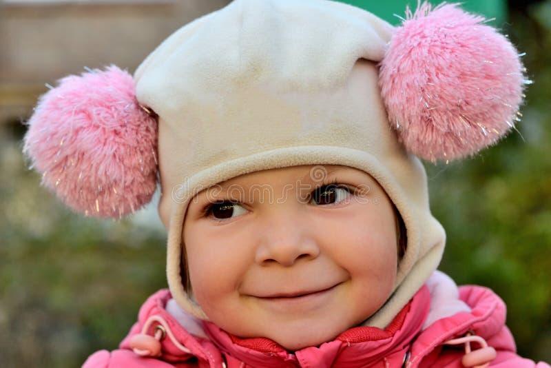 Retrato de un bebé sonriente en un sombrero rosado imágenes de archivo libres de regalías